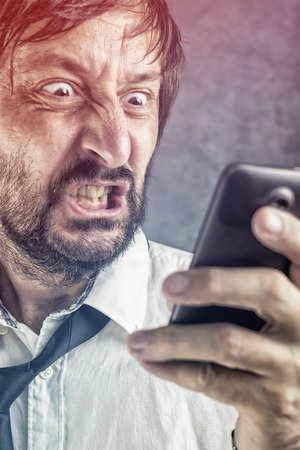 offend: Portrait of angry businessman received frustrating SMS message or e-mail on mobile smart phone, selective focus on face