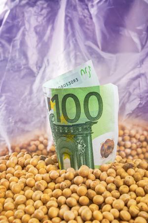 planta de frijol: Hacer ganancias en la agricultura comercial del cultivo de la soja - planta de soja, vainas y frijoles cosechados a finales del verano del campo cultivado con billetes en euros, el enfoque selectivo