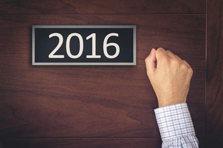door: New Year 2016 Resolutions, Businessman Knocking on the Door with Number 2016. Stock Photo