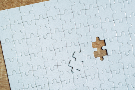 final piece of the puzzle: Piece missing from jigsaw puzzle as copy space placed on top of old wooden oak table, top view