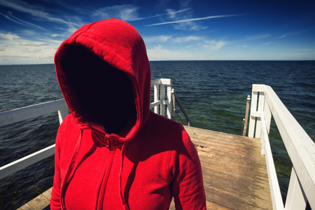 seized: Abduction Concept, Faceless Hooded Unrecognizable Woman at Ocean Pier, Unknown Spooky Female in Red Shirt