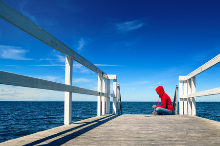 alone: Alone Young Adult Woman Texting SMS Messages on Smart Phone while Sitting at the Edge of Wooden Ocean Pier Stock Photo
