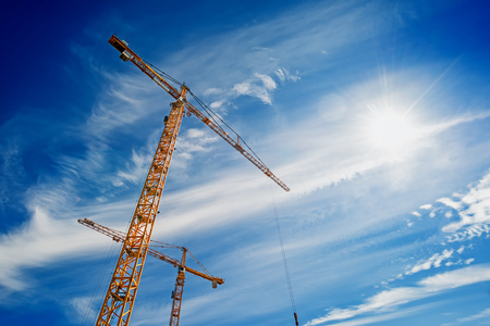 cantieri edili: Two Yellow Industrial Cranes Working on Construction Site Against Blue Sky