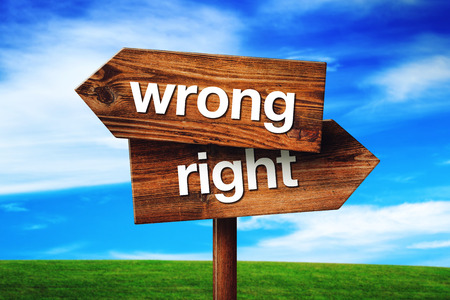 the right choice: Wrong or Right Choice, Rustic Opposite Direction Wooden Sign on Grassland Field Stock Photo