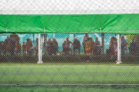 defocussed: Unrecgonizable audience watching kids playing soccer game