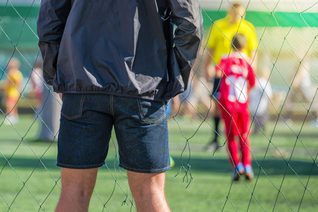 Father watching son playing soccer game, kids playing football, selective focus