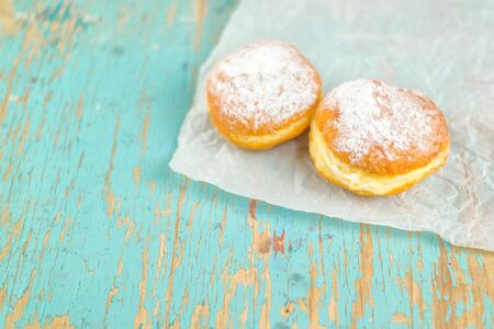 desayuno romantico: Sweet sugary donuts on rustic wooden kitchen table, tasty bakery doughnuts on crumpled baking paper in vintage retro toned image Foto de archivo