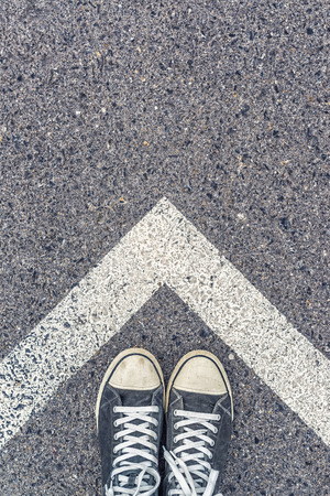 pavement: Man standing above arrow shaped line sign on urban pavement, top view of young male feet wearing sneakers, guidance concept, getting around unknown city, getting directions