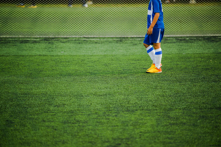 sports field: Kid playing soccer, unrecognizable boy in blue jersey standing of football pitch
