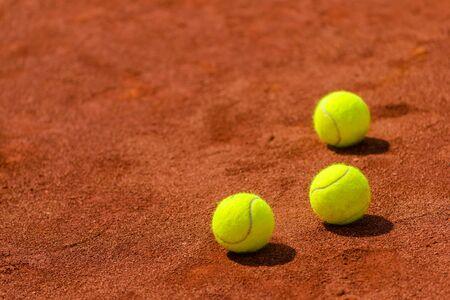 balones deportivos: Pelotas de tenis en tierra batida, con copia espacio como fondo el deporte, el enfoque selectivo Foto de archivo