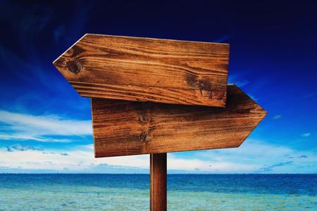 seaside resort: Direction signpost on seaside beach, rustic wooden blank sign in summer vacation resort Stock Photo