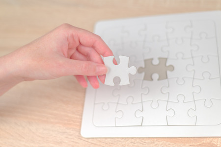 inteligent: Female hand putting a missing piece and solving blank white jigsaw puzzle placed on top of old wooden oak table, close up, selective focus