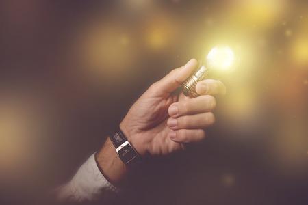 Big business idea visual metaphor, businessman with light bulb lightning up the dark office interior, retro toned image, selective focus.