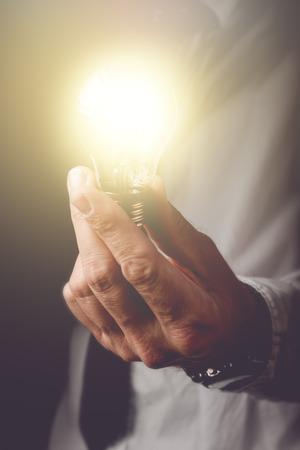 La educación de las nuevas ideas a la empresa, el empresario con la bombilla que ofrece nuevas soluciones a la comprensión de los problemas en los negocios, en tonos retro de imagen, enfoque selectivo. Foto de archivo - 46792536