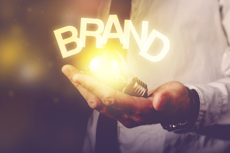 brands: Brand idea concept with businessman holding light bulb, retro toned image, selective focus. Stock Photo