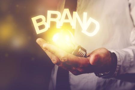 Brand idea concept with businessman holding light bulb, retro toned image, selective focus. Stockfoto
