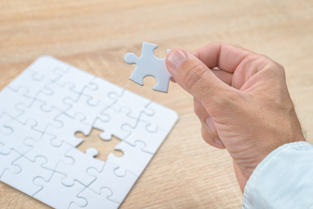 business puzzle: Businessman hand putting a missing piece and solving blank white jigsaw puzzle placed on top of old wooden oak table, close up, selective focus Stock Photo
