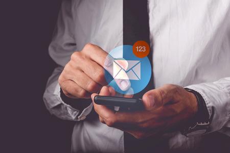 comunicarse: El hombre de negocios a ver los mensajes de correo electrónico en el teléfono móvil inteligente, el dedo en la pantalla táctil del dispositivo inalámbrico empujando icono de la aplicación, imagen retro tonos, enfoque selectivo Foto de archivo
