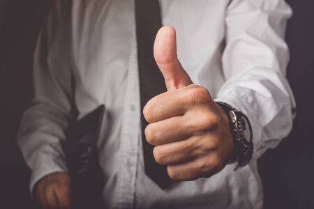 endorsement: Businessman gesturing thumbs up sign for endorsement and approval, retro toned image, selective focus Stock Photo