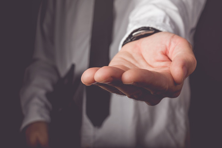lend a hand: Businessman requesting for money loan, retro toned image, selective focus Stock Photo