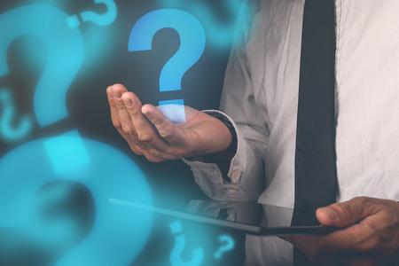 auditor�a: Hombre de negocios con preguntas, hombre de negocios con la tableta digital que sostiene signo de interrogaci�n, la imagen retro tonos, enfoque selectivo