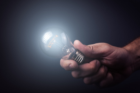 innovation: Creative enlightenment, understanding and generating new ideas, innovator and inventor with hand holding light bulb, retro toned image, selective focus.