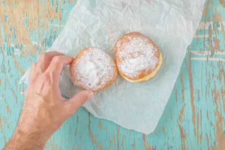 hannukah: Male hand reaches and picking sweet sugary donut from rustic wooden kitchen table, classic hannukah sufganiyot or tasty bakery doughnuts overhead shot, top view Stock Photo