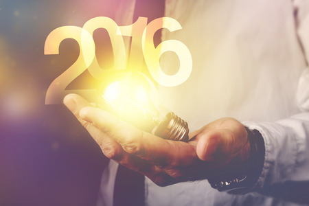 business plan: Happy new 2016 business year, businessman with light bulb and number 2016, retro toned image, selective focus.