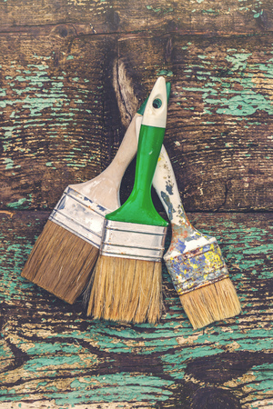 used: Old used paintbrush for acrylic painting on rustic wooden board, retro toned with blank copy space