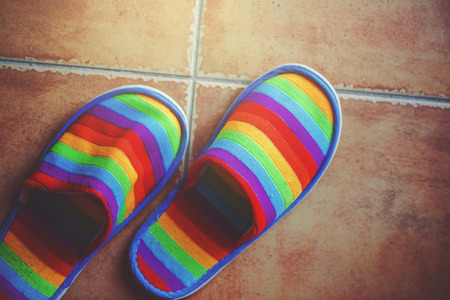 deliverance: Retro toned rainbow color pattern slippers on ceramic tiled floor with natural daylight from the window, LGBT pride and coming out of closet concept, top view Stock Photo