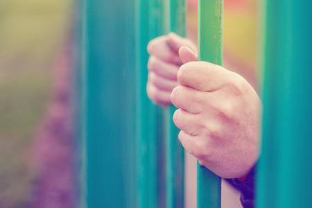 isolation: Person behind bars, female hands gripping steel bars, concept of captivity and imprisonment, retro toned, selective focus
