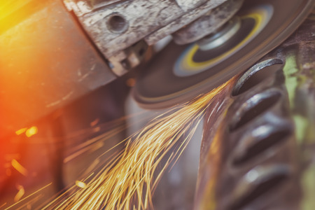 electrical safety: Worker grinding steel pipe, man using grinder to work on piece of metal in workshop, grinding sparks flying around, retro toned image with selective focus Stock Photo