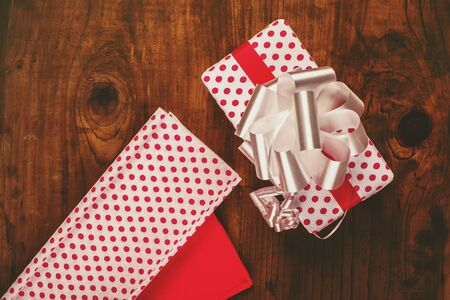 polka dotted: Christmas gifts and presents wrapping, wrapped ox with bow tie and decorative polka dotted paper on wooden desk, top view, retro toned