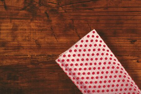 polka dotted: Christmas gifts and presents wrapping, decorative polka dotted paper on wooden desk, top view, retro toned Foto de archivo