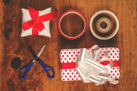 polka dotted: Christmas gifts and presents wrapping, assorted decorative polka dotted paper, scissors and ribbon tapes on wooden desk, top view, retro toned