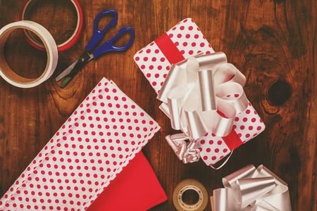 polka dotted: Christmas gifts and presents wrapping, decorative polka dotted paper, scissors and ribbon tapes on wooden desk, top view, retro toned