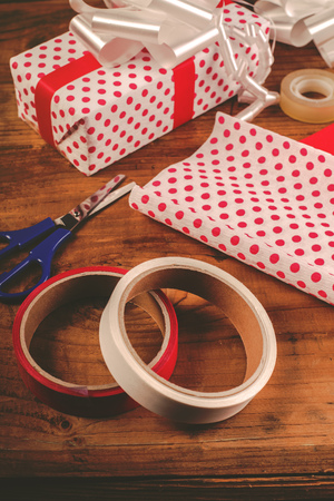 polka dotted: Christmas gifts and presents wrapping, decorative polka dotted paper, scissors and ribbon tapes on wooden desk, retro toned
