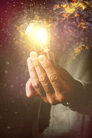 Energy of new ideas in business process, businessman with light bulb as metaphor of new ideas, innovation and creativity, retro toned image, selective focus. Stock Photo