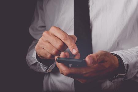 モバイルのスマート フォン、トーン、レトロのワイヤレス デバイスのタッチ スクリーン上の指画像、選択と集中に取り組んでの実業家
