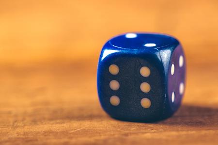 dados: Macro foto de dados azules en la mesa de madera con el número seis de revestimiento, retro tonos, enfoque selectivo