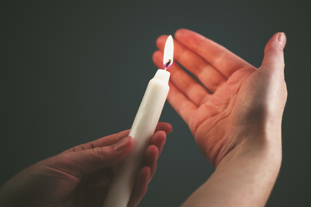 christian candle: Female hands with burning candle in the dark, woman lighting up the candle as religious ceremony Stock Photo