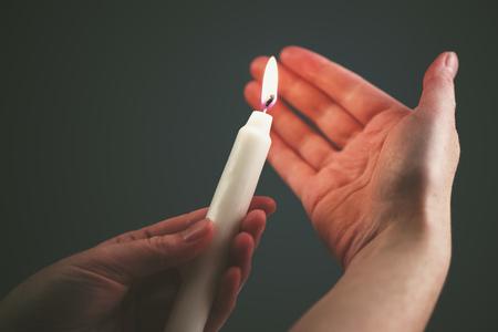 feier: Weibliche Hände mit brennenden Kerze in der Dunkelheit, Frau zündet die Kerze als religiöse Zeremonie nach oben