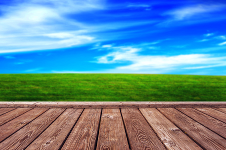 grassfield: Empty Rustic Wooden Boardwalk Deck and Open Grassfield as Abstract Natural Background for Product Placement Backdrop Stock Photo