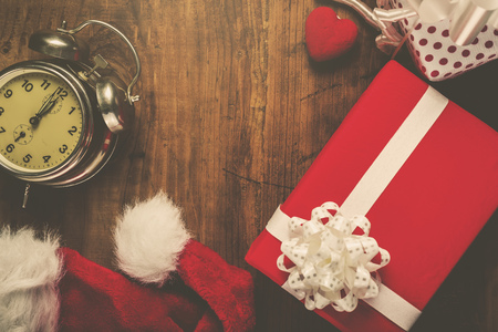 last minute: Christmas and New Year holiday, Santa Claus hat, presents, gifts and vintage clock at midnight, top view, retro filter toned image