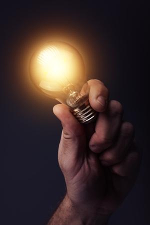 창조적 인 에너지와 새로운 아이디어, 혁신 및 창의력 전구, 복고풍 톤된 이미지, 선택적 포커스를 들고 손으로.