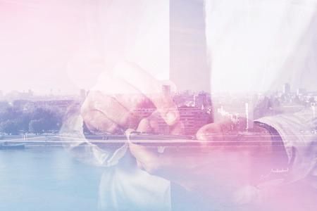 empresas: Doble exposición de manos de negocios con el teléfono móvil inteligente, el dedo en la pantalla táctil del dispositivo inalámbrico, paisaje urbano en el fondo, imagen retro tonos, enfoque selectivo