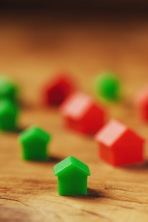 mortgage: Macro shot of miniature plastic houses on wooden table as mortgage concept, selective focus