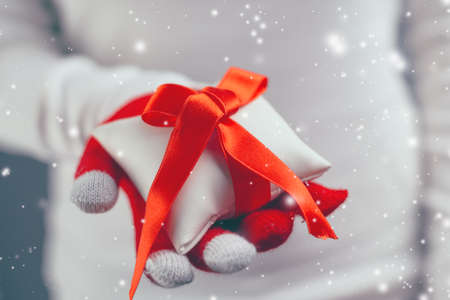 benevolent: Woman giving Christmas gift wrapped with red ribbon decoration, holiday season with snowflakes falling, retro toned image with selective focus