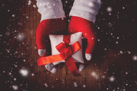 Christmas eve gift, hands giving wrapped present, top view retro toned image with selective focus