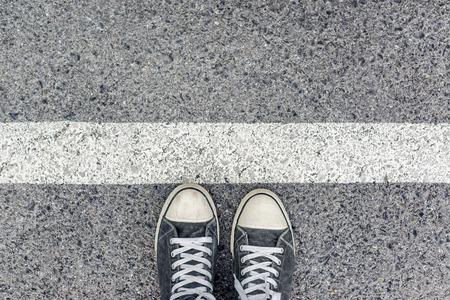 都市道路舗装面の境界線に立っている男は、ライン、入国管理の概念の背後に待機しているスニーカーを身に着けている若い男性の足の平面図